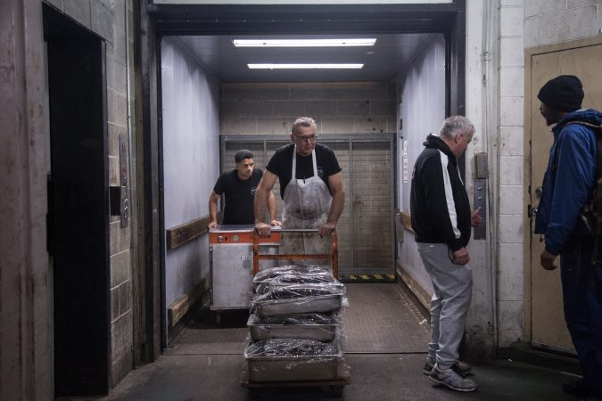 Andy Wash, center, brings up  six double pans and four single pans of Pastrami which has been cured in-house in the market basement, as Nate Ventura, left, follows behind with an extra oven which will be placed inside the deli to help accommodate the demand in preparation for the anticipated influx of customers coming from the first day of the Philadelphia Flower Show the next day. (Emily Cohen for WHYY)