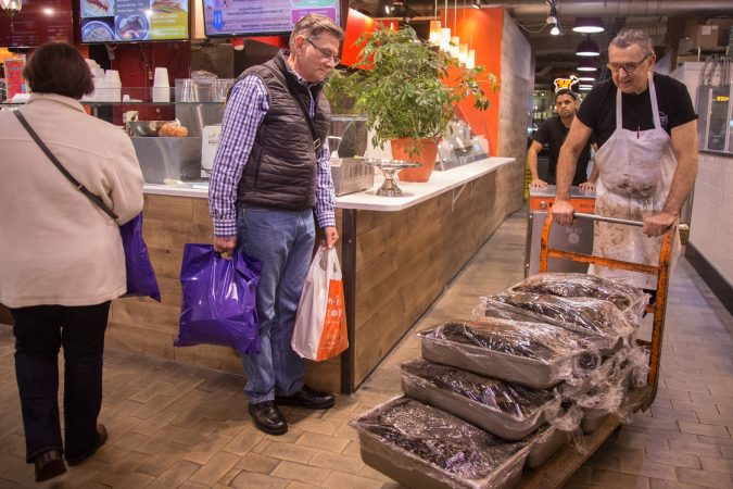 A market patron watches as Andy Wash, right, brings up six double pans and four single pans of Pastrami which has been cured in-house in the market basement, as Nate Ventura, behind, follows behind with an extra oven which will be placed inside the deli to help accommodate the demand in preparation for the anticipated influx of customers coming from the first day of the Philadelphia Flower Show the next day. (Emily Cohen for WHYY)