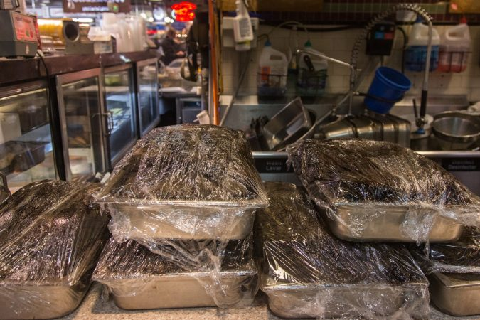 Pans of Pastrami sit on the countertop waiting to be placed into an oven. In anticipation for an influx of customers from the Flower Show, Hershel's East Side Deli has doubled their meat preparation. (Emily Cohen for WHYY)