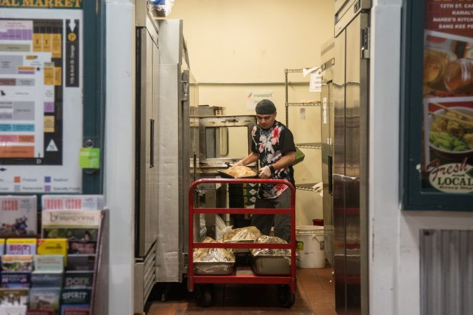 """It's 5am and Jhovani """"G"""" Posada, 37, removes the cooked meat from their ovens to prep them for the morning rush. (Emily Cohen for WHYY)"""