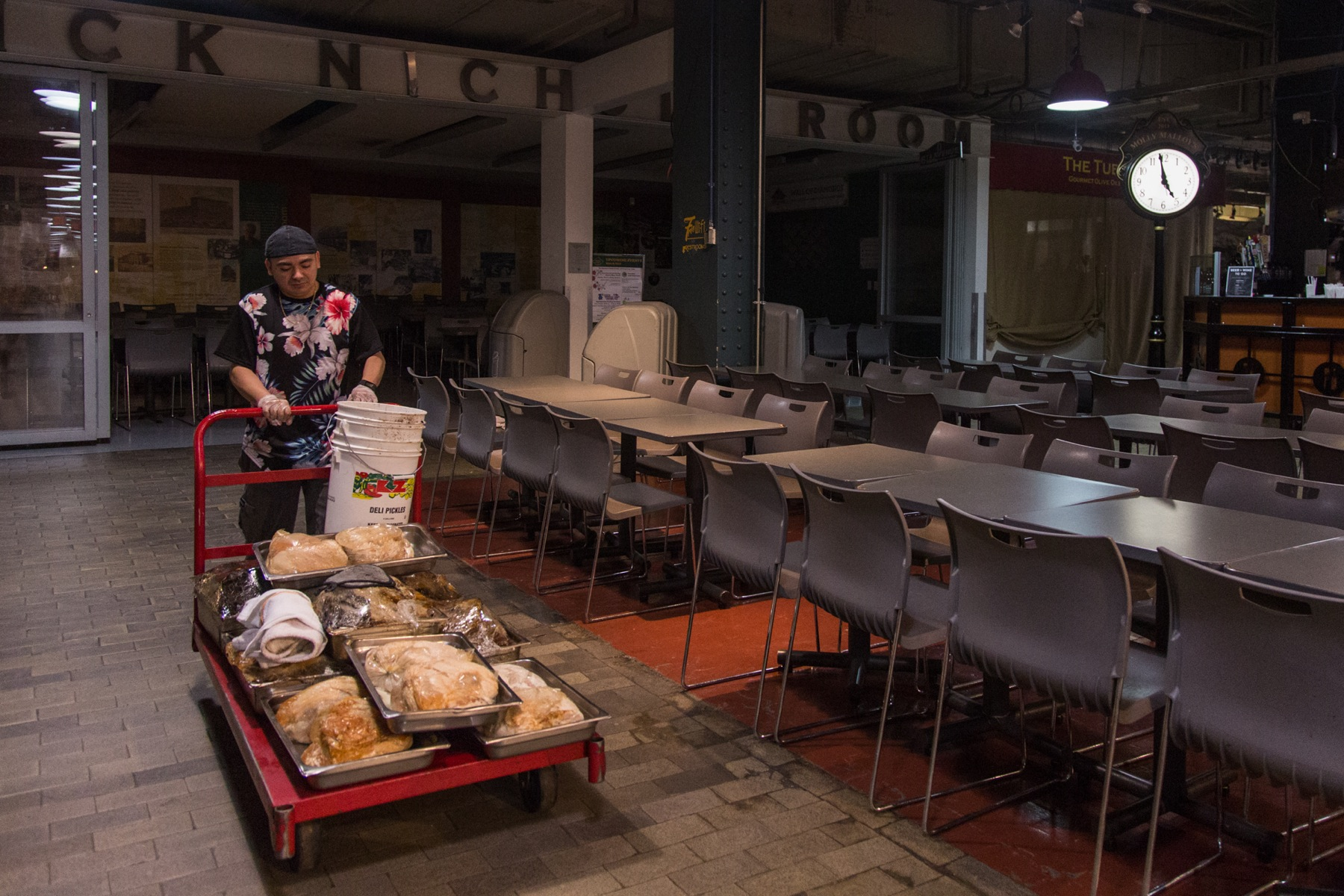 """At 5 a.m., Jhovani """"G"""" Posada, 37, brings freshly cooked meats from the oven to the deli."""