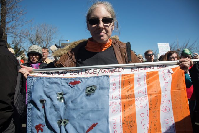 Debbie Collins, of Upper Providence, holds up her 3x5 flag which is completely covered with the dates of school shootings from all over the country and their number of victims in circles; the flag is full. (Emily Cohen for WHYY)