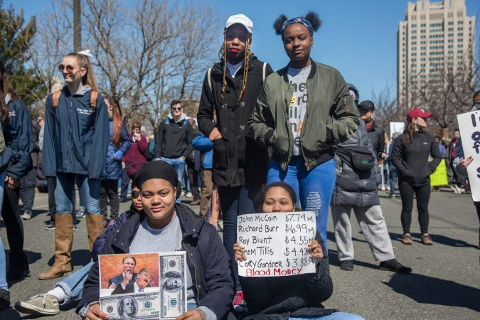 A group of friends sit and stand as they listen to the speakers at the Philadelphia March for Our Lives, March 24, 2018. (Emily Cohen for WHYY)