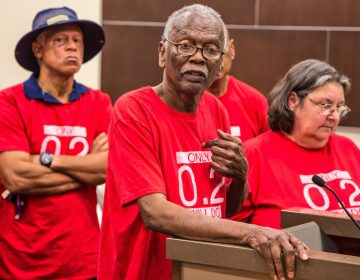 Robert Taylor, (center), speaks at a St. John the Baptist Parish council meeting in 2017. He and the other members of the citizens' group around him wear T-shirts that reference the safety limit for the chemical chloroprene. (Julie Dermansky)
