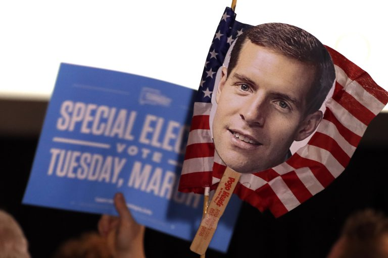Supporters of Conor Lamb hold signs during his election night party
