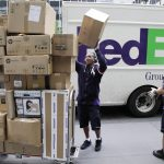 FedEx workers sort boxes for delivery on a busy street.