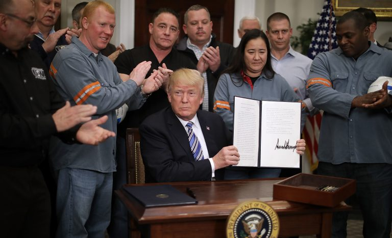 Surrounded by steel and aluminum workers, President Trump holds up the order on steel imports that he signed in Roosevelt Room the the White House on Thursday. (Chip Somodevilla/Getty Images)