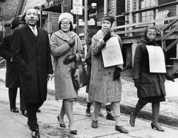 Dr. Martin Luther King, Jr., left, and his wife, Coretta Scott King, second from left, join pickets during a tour of an Atlanta slum area