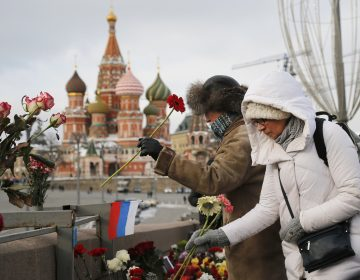 People lay flowers at the place where Russian opposition leader Boris Nemtsov was gunned down, next to the Kremlin Wall, in Moscow, Russia, Sunday, Feb. 25, 2018. Thousands of Russians took to the streets of downtown Moscow to mark three years since Nemtsov was gunned down outside the Kremlin. (AP Photo/Alexander Zemlianichenko)