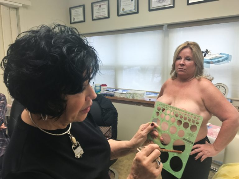 Rose Marie Beauchemin Verzella uses a template to pick the size of Maureen Matteis-Bilbee's nipple and areola tattoos. (Alex Stern for WHYY)