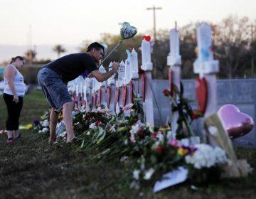 Paul Birmingham, on Monday, Feb. 19, 2018, writes on a cross placed in memory of student Gina Montaldo outside of Marjory Stoneman Douglas High School