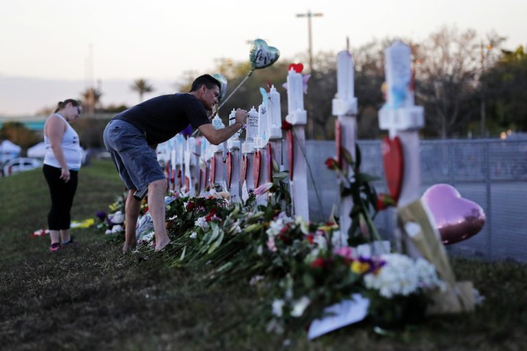 Paul Birmingham, on Monday, Feb. 19, 2018, writes on a cross placed in memory of student Gina Montaldo outside of Marjory Stoneman Douglas High School