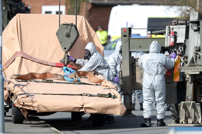 Soldiers wearing protective clothing prepare to lift a tow truck in Hyde Road, Gillingham, Dorset, England as the investigation into the suspected nerve agent attack on Russian double agent Sergei Skripal continues Wednesday March 14, 2018.  The army cordoned off a road in Dorset on Wednesday as the investigated the attack on Sergei Skripal and his daughter Yulia. Authorities have cordoned off several sites in and near Salisbury, 90 miles (145 kilometers) southwest of London as part of their probe.  (Andrew Matthews/PA via AP)