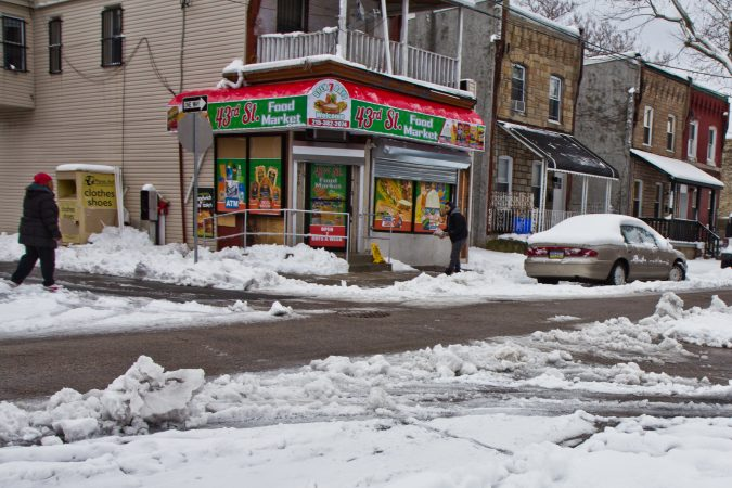 Residents and business owners salt sidewalks Thursday morning in West Philadelphia. (Kimberly Paynter/WHYY)