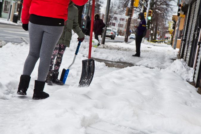 Residents clean up after the snow Thursday morning in West Philadelphia. (Kimberly Paynter/WHYY)