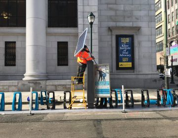 A Streets Department worker affixes a solar panel to an Indego station on Chestnut Street. (City of Philadelphia/ Office of Transportation and Infrastructure Systems)