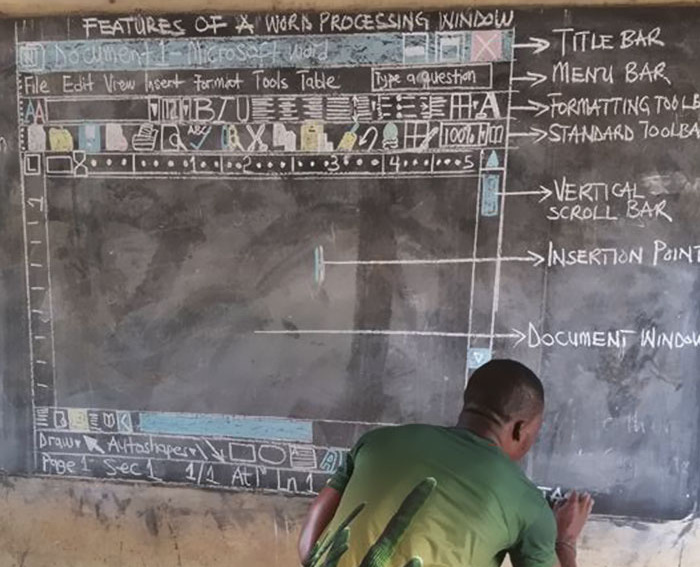 Owura Kwadwo Hottish illustrates a window of Microsoft Word using colored chalk on a blackboard. He uses it to teach computer skills to students at the Betenase M/A Junior High School in Kumasi, Ghana. (Frimpong Innocent)