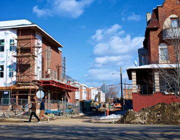 Two young men walk past a rehab project in Strawberry Mansion, in 2018.