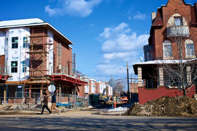 Two young men walk past a rehab project in Strawberry Mansion.