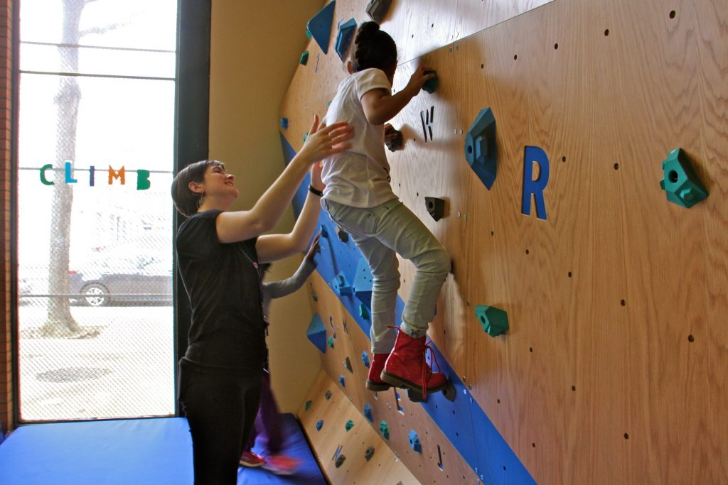 Librarian Kayla Hoskinson helps Aryanna Ross, 6, negotiate the climbing wall at the Cecil B. Moore library.