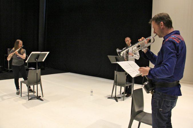 Performing Schönheit, (from left) Emma Resmini, flute, Sean Bailey, bass clarinet, and Marco Blaauw,  trumpet, rehearse on the Fringe Arts stage. (Emma Lee/WHYY)