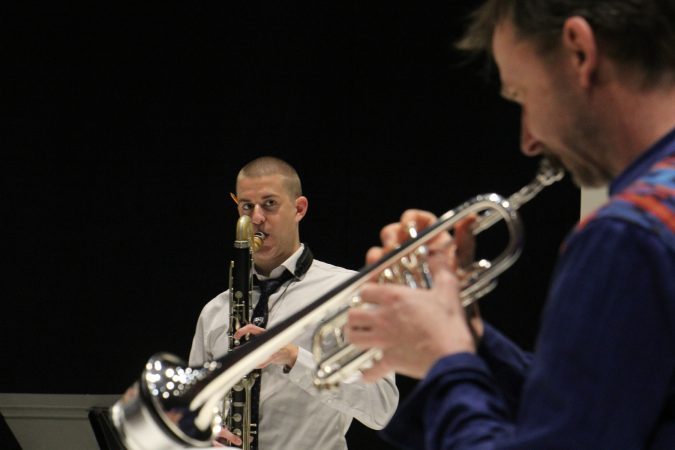 Bass clarinetist Sean Bailey keeps an eye on Marco Blaauw during a rehearsal for Karlheinz Stockhausen's cycle, Klang. (Emma Lee/WHYY)