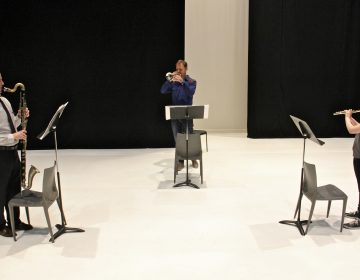 Performing Schönheit, (from left) Sean Bailey, bass clarinet, Marco Blaauw, trumpet, and Emma Resmini, flute, rehearse on the Fringe Arts stage. (Emma Lee/WHYY)