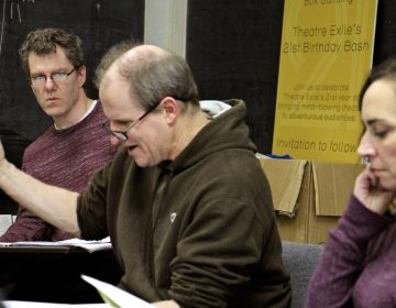 Playwright Michael Hollinger (left) listens to a first read of a new script during rehearsal for his drama,