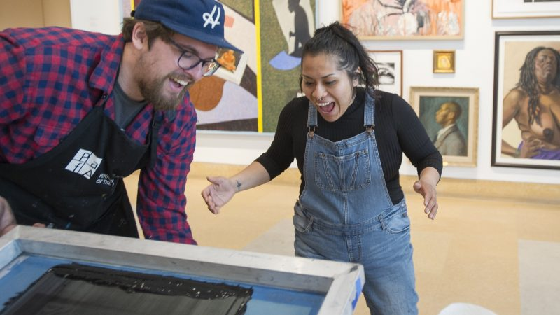 Ben Grzenia assists Jessica Aquino in creating a silk screen protest print. (Jonathan Wilson for WHYY)