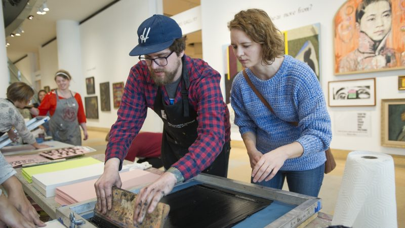 Ben Grzenia shows Kristina Murray how to squeegee a silk screen print. (Jonathan Wilson for WHYY)