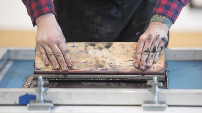 Ben Grzenia demonstrates how to squeegee a silk screen print. (Jonathan Wilson for WHYY)