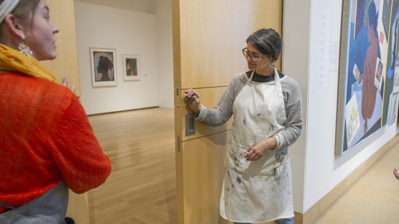 On the last day of the Chuck Close Exhibit, MFA printmaking students Candace Jensen left, and Melissa Joseph close the exhibit doors. MFA students and museum staff then proceeded to cover the doors with protest posters. (Jonathan Wilson for WHYY)