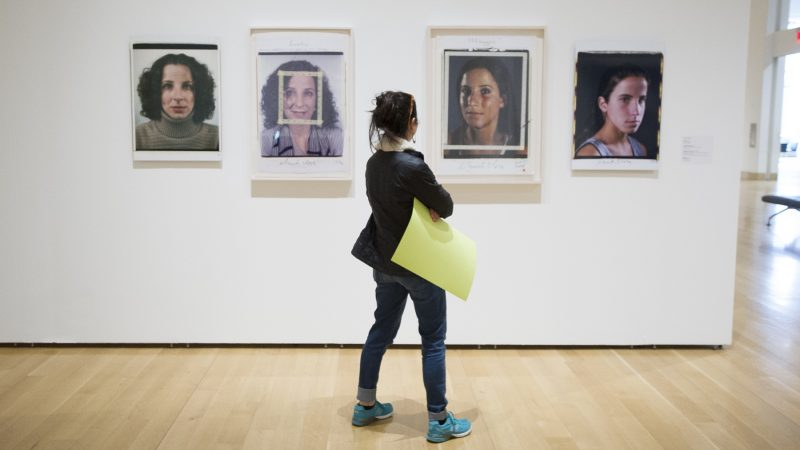 Tamara Weiss carries her protest poster with her as she views the Chuck Close Exhibit. (Jonathan Wilson for WHYY)