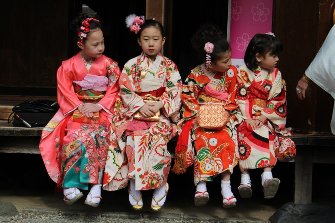 Students from the Japanese Language School of Philadelphia (from left) Julia Epps, 8, Suzu Noda, 8, Julia Casey, 7, and Alyssa Casey, 5, wait to play their part in the opening ceremony for the Cherry Blossom Festival at the Japanese House and Garden in Fairmount Park. (Emma Lee/WHYY)
