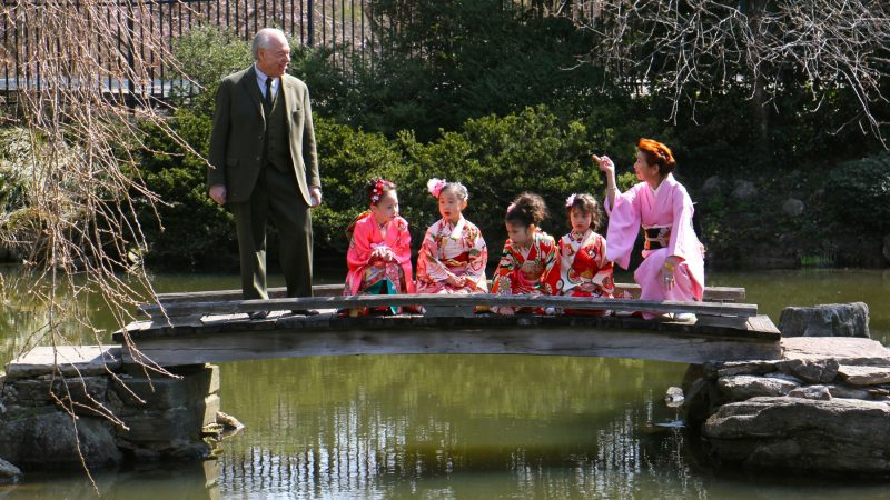Joseph Zuritsky (left) who donated his prized koi fish to the Shofuso Japanese House and Garden in Fairmount Park, participates in a Cherry Blossom Festival event with students from the Japanese Language School of Philadelphia. (Emma Lee/WHYY)