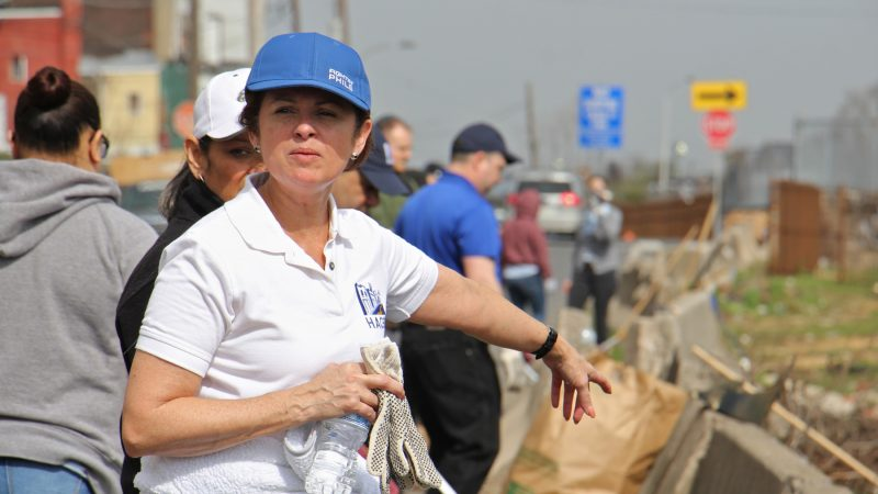 Maria Gonzalez, president of HACE, directs cleanup efforts along Gurney Street near the Conrail tracks, site of a former heroin encampment. (Emma Lee/WHYY)