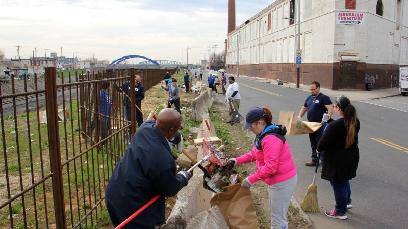 About 30 workers and volunteers clean up trash along Gurney Street near the former site of a notorious heroin encampment. (Emma Lee/WHYY)
