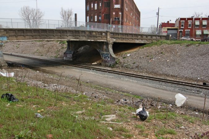 The site of the former heroin camp along the Conrail tracks and under the A Street bridge, has been cleaned and fenced off. (Emma Lee/WHYY)