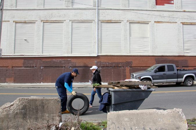 Workers and volunteers pick up trash along Gurney Street near the former heroin encampment. The Jerusalem furniture warehouse across the street is being considered for a mural, part of a strategy of using art to reclaim the space. (Emma Lee/WHYY)