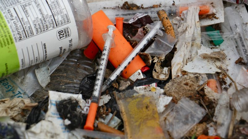 Hundreds of syringes were found during the cleanup of the block-long stretch of grass between Gurney Street and the Conrail tracks. (Emma Lee/WHYY)