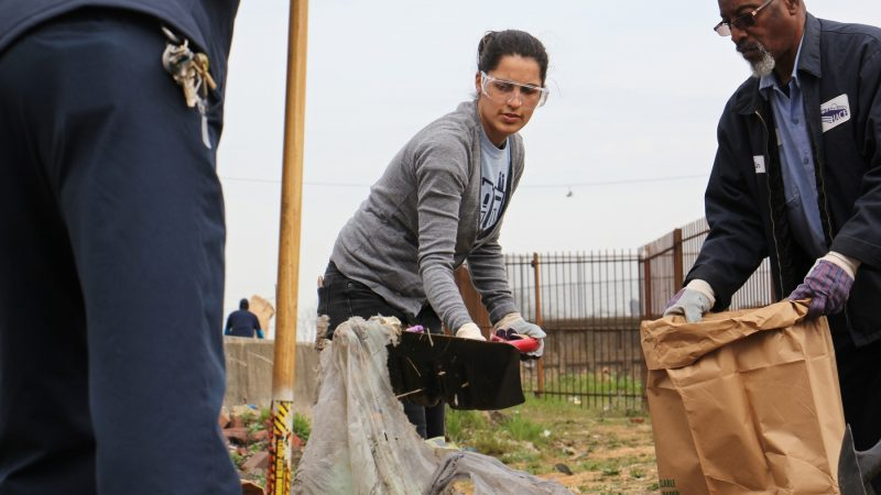 Stasia Monteiro of HACE shovels garbage into a bag during the Gurney Street cleanup. (Emma Lee/WHYY)