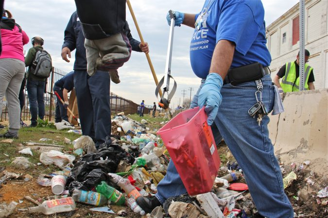 Tony Beltram of HACE separates the syringes from the rest of the trash. Hundreds of used syringes were found during the cleanup of a block-long stretch of grass between Gurney Street and the Conrail tracks. (Emma Lee/WHYY)
