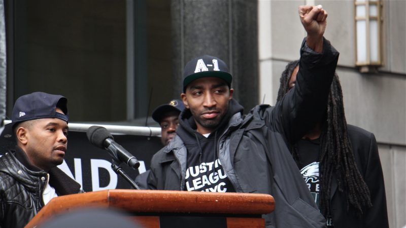 Hip-hop artist Mysonne Linen (center), who spent seven years in prison, supports Meek Mill during a rally, sharing the stage with activist lawyer Angelo Pinto (left). (Emma Lee/WHYY)