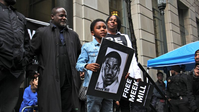 Meek Mill's son, Papi, accompanied by his grandmother, the rapper's mother Kathy Williams, takes the stage during a rally outside the Criminal Justice Center. (Emma Lee/WHYY)