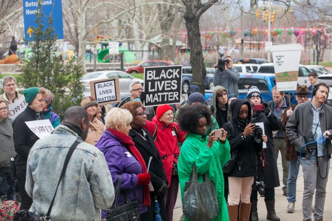 Demonstrators gather in front of the Philadelphia Police Department Headquarters Thursday before marching up Market Street in response to an incident where two black men who were arrested in a Center City Starbucks last week. (Brad Larrison for WHYY)