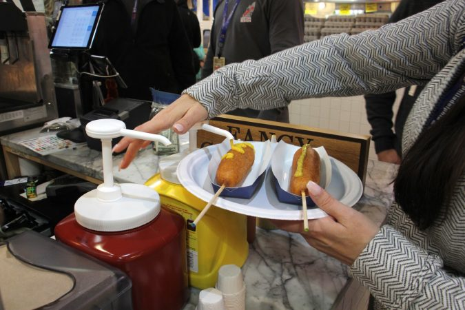 A customer adds mustard to corn dogs at Fox and Son at Reading Terminal Market. (Emma Lee/WHYY)