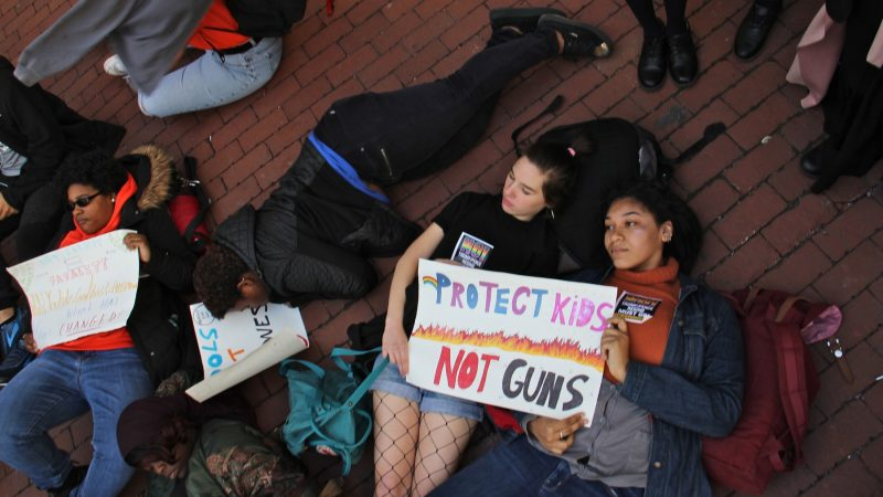 CAPA high school students (from right) Jordan Gibson and Alexandra Britton, participate in a die-in at Philadelphia City Hall, part of a national day of protest against gun violence on the 19th anniversary of the Columbine school shooting. (Emma Lee/WHYY)