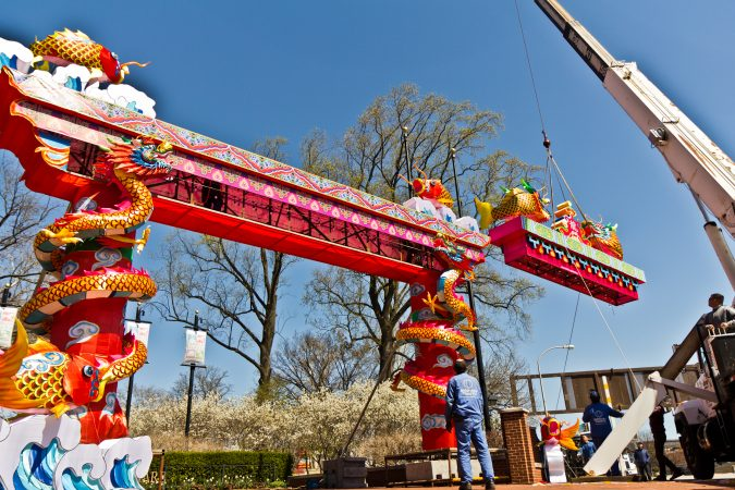 The top of the entryway arch is lifted by crane Friday afternoon. (Kimberly Paynter/WHYY)