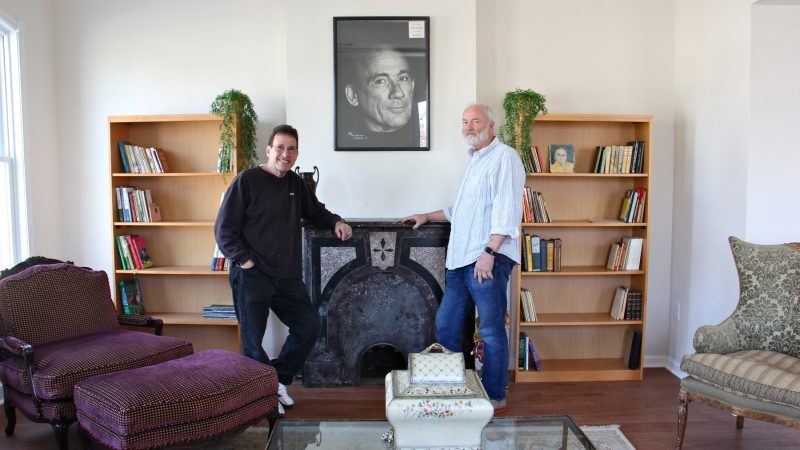 George Vallianos (left), president of the Nick Virgilio Haiku Association, and board member Henry Brann, stand beneath a portrait of the poet at the Nick Virgilio Writers House in Camden. (Emma Lee/WHYY)