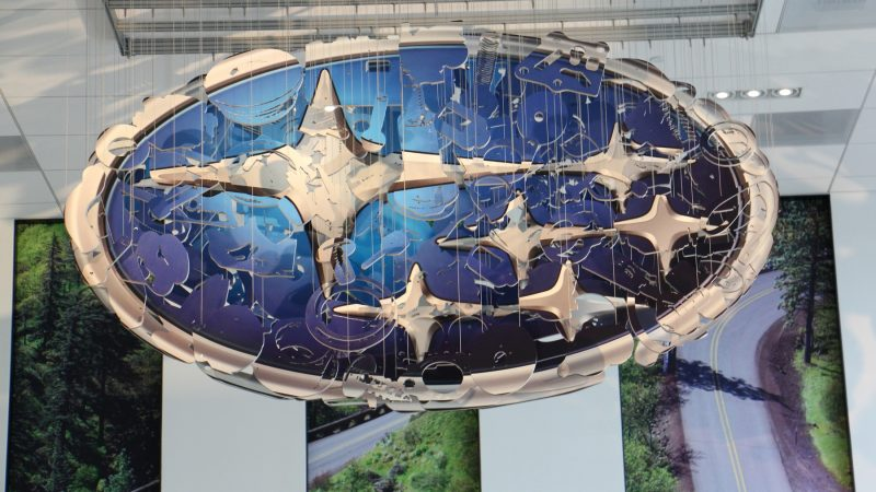 A sculpture of car parts hanging from the ceiling of the lobby resolves itself into the Subaru logo when viewed from the correct point. (Emma Lee/WHYY)